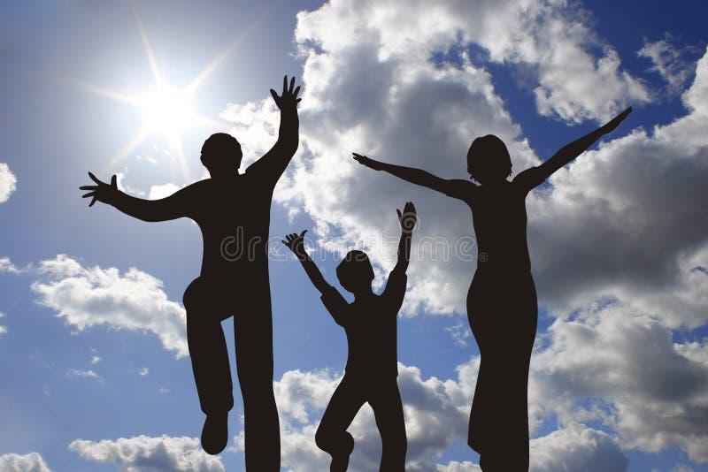 Silhueta feliz da família no céu ensolarado imagem de stock