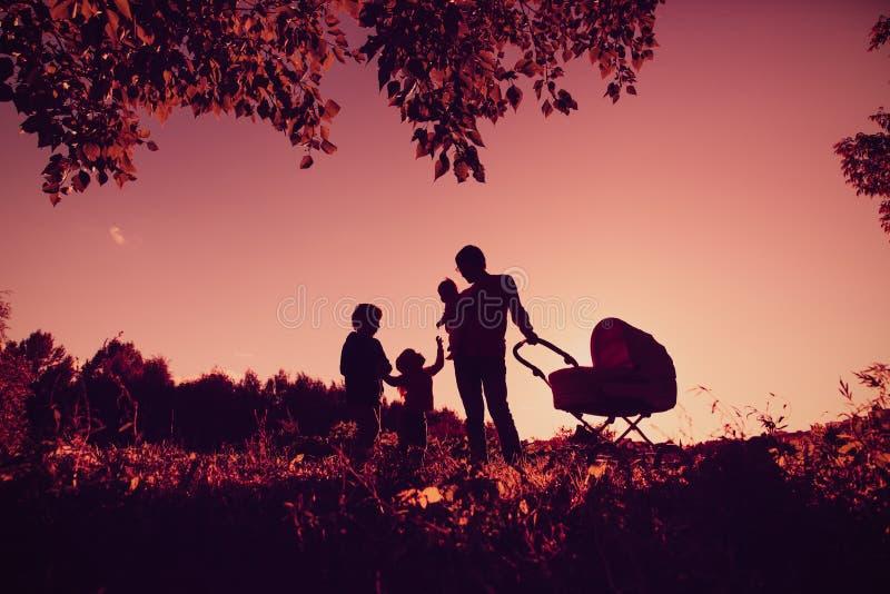 A silhueta feliz do conceito de família do pai com árvore caçoa no céu do por do sol foto de stock royalty free