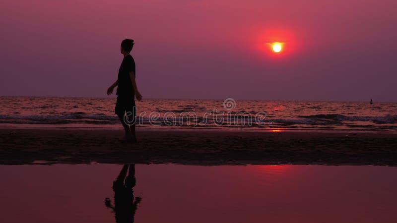 Silhueta Homem novo asiático só que anda pacificamente ao longo de uma praia abandonada no por do sol Seascape imagem de stock royalty free