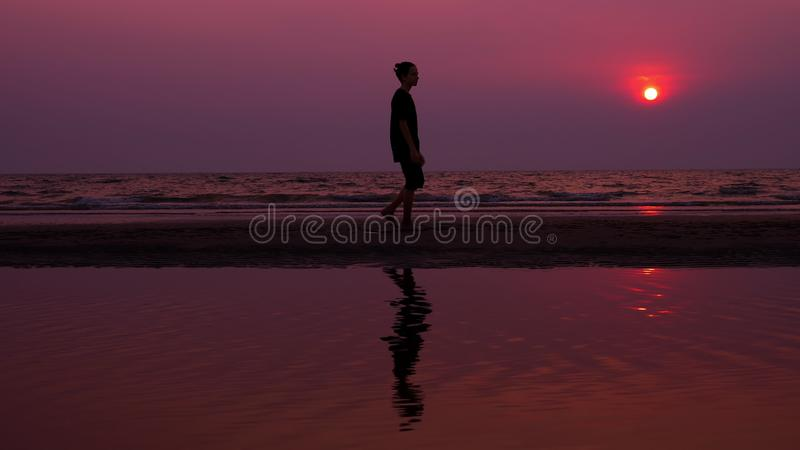 Silhueta Homem novo asiático só que anda pacificamente ao longo de uma praia abandonada no por do sol Seascape imagem de stock