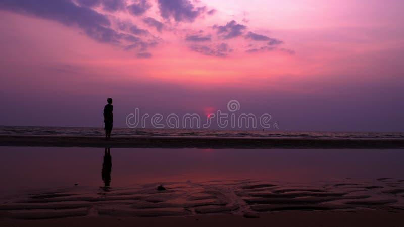 Silhueta Homem novo asiático só que anda pacificamente ao longo de uma praia abandonada no por do sol Seascape fotografia de stock