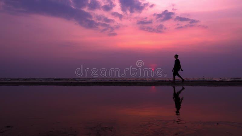 Silhueta Homem novo asiático só que anda pacificamente ao longo de uma praia abandonada no por do sol Seascape foto de stock