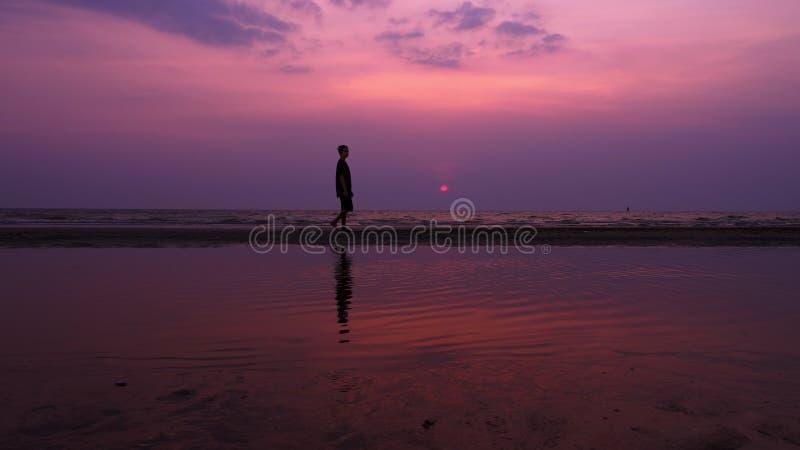 Silhueta Homem novo asiático só que anda pacificamente ao longo de uma praia abandonada no por do sol Seascape foto de stock royalty free