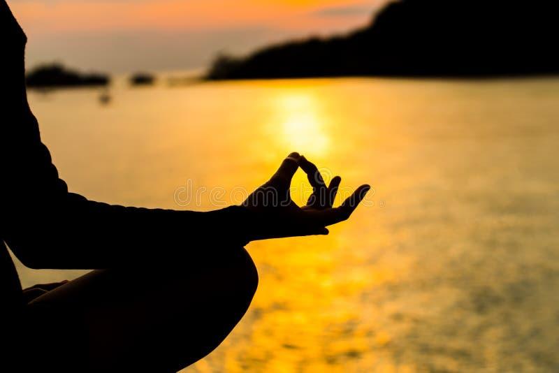 Silhueta, mão da mulher que meditam na pose da ioga ou Lotus Posit fotografia de stock royalty free
