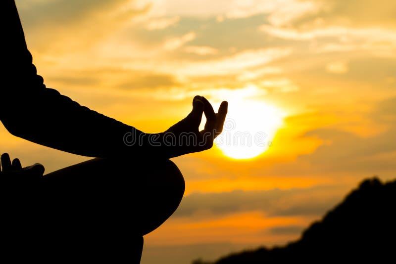 Silhueta, mão da mulher que meditam na pose da ioga ou Lotus Posit imagens de stock royalty free