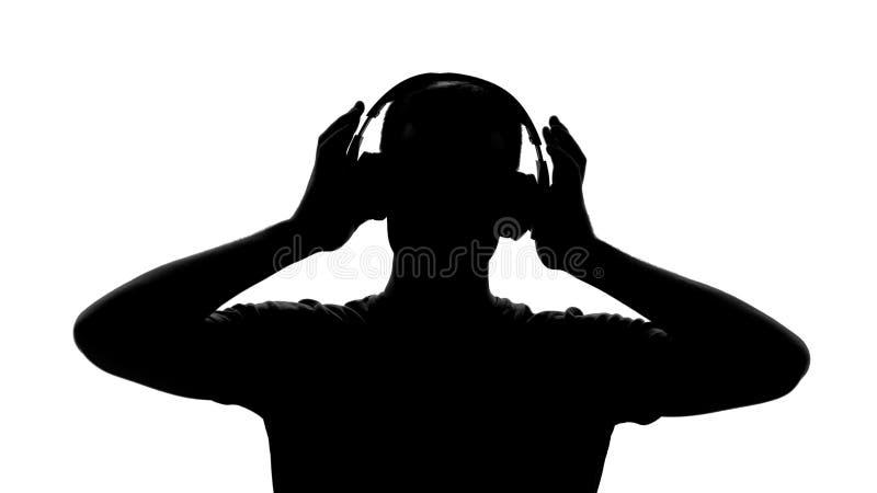 Silhueta masculina com os fones de ouvido que escutam a música, apreciando a melodia, inspiração fotografia de stock