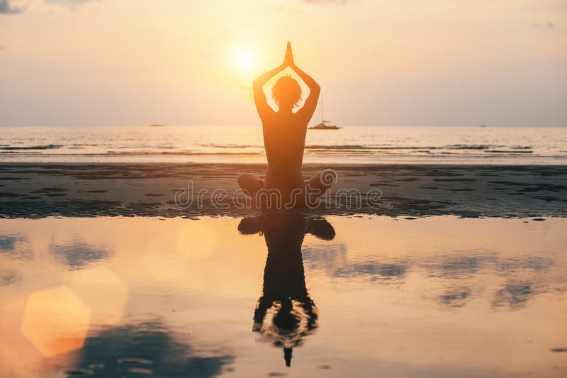Silhueta na praia, por do sol brilhante da mulher da ioga relaxe imagem de stock