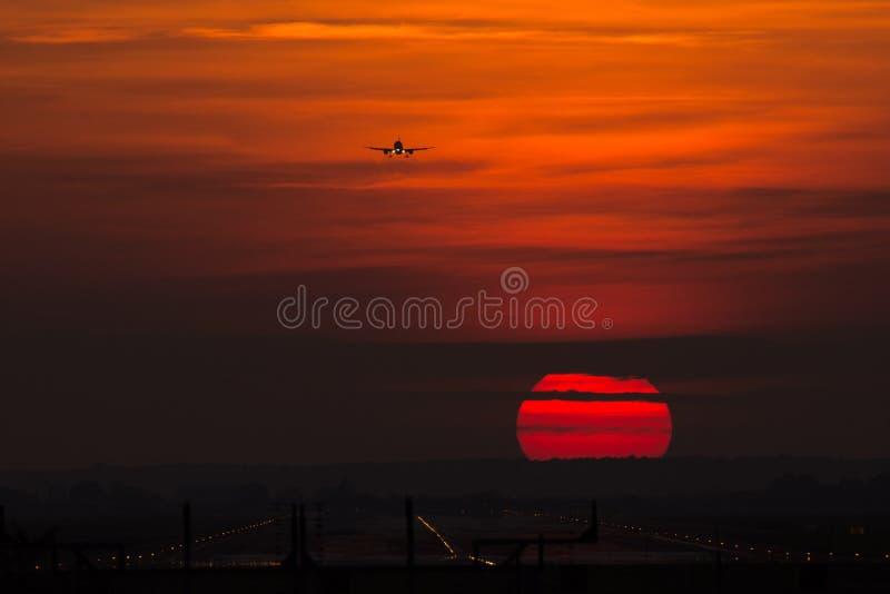 Silhueta no sol, aproximação final do avião na aterrissagem da pista de decolagem fotografia de stock royalty free