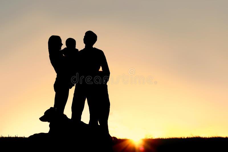 Silhueta nova feliz da família e do cão no por do sol foto de stock