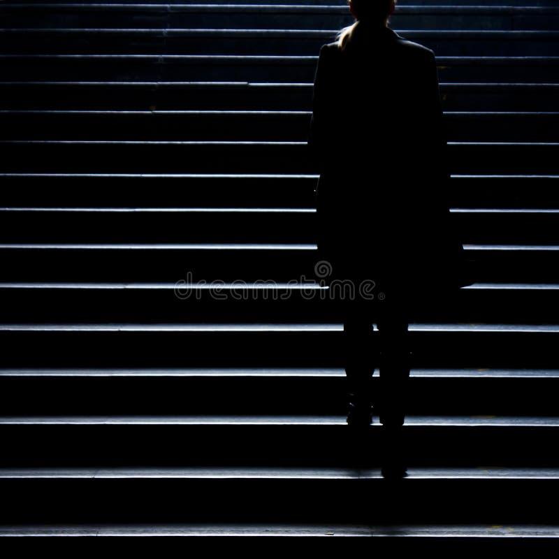 Silhueta obscura da mulher elegante nova que escala acima o st da cidade fotografia de stock