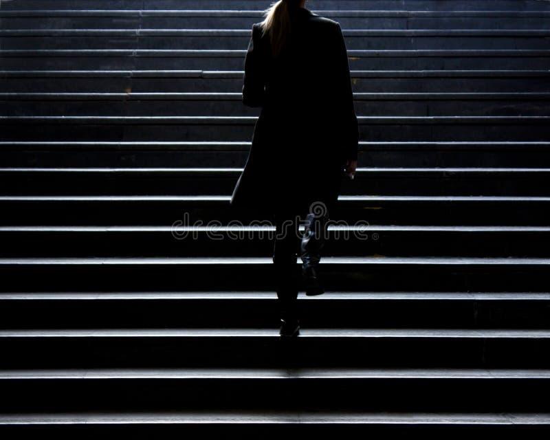 Silhueta obscura da mulher elegante nova que escala acima o st da cidade foto de stock royalty free