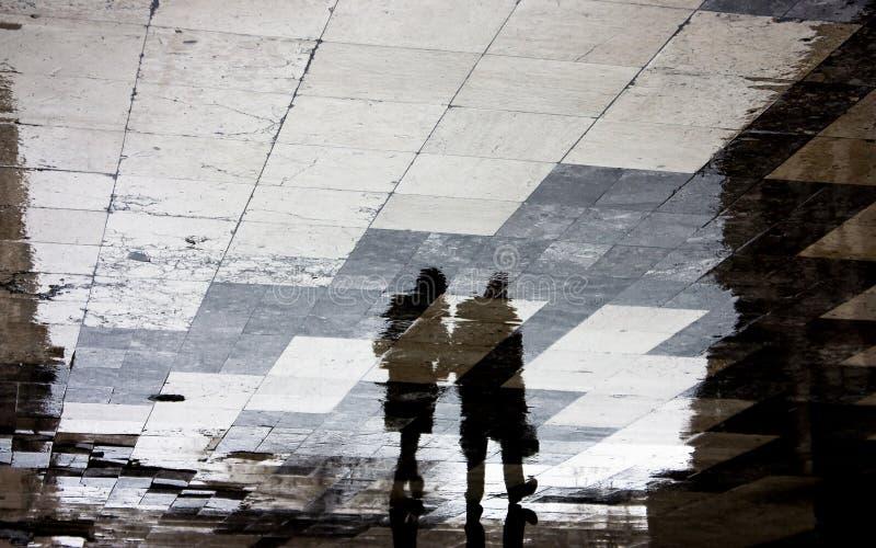 Silhueta obscura da reflexão de dois povos que andam junto em t foto de stock