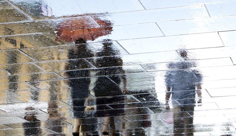 Silhueta obscura da reflexão dos povos que andam chuvosa e do sunn fotos de stock