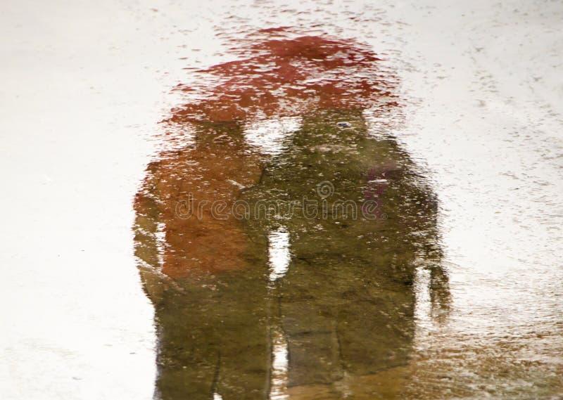 Silhueta obscura da reflexão em uma poça dos pares que guardam as mãos fotografia de stock