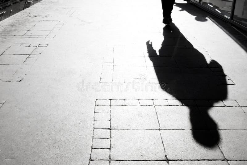 Silhueta obscura da sombra de um passeio da pessoa fotos de stock