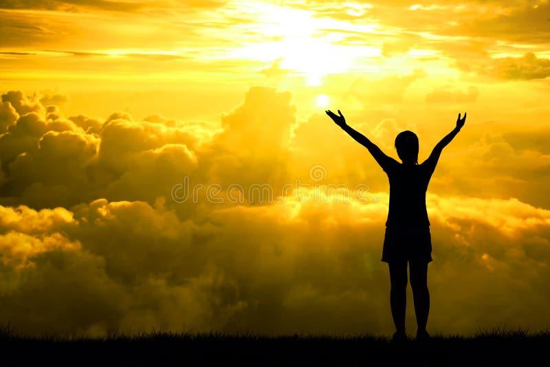 A silhueta ou backlit de mulheres do esporte abre os braços aumentados para no céu da esperança no efeito da luz do por do sol, c fotos de stock