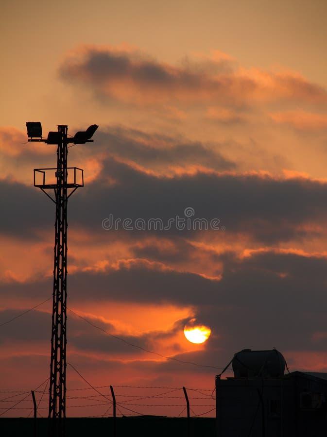 Silhueta para o nascer do sol com torre clara imagem de stock