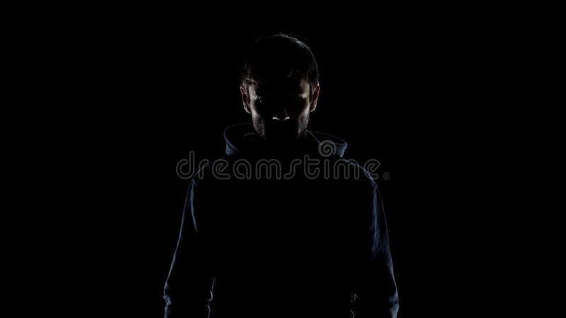 Silhueta preta da capa vestindo do homem misterioso, intenção cometer o crime foto de stock
