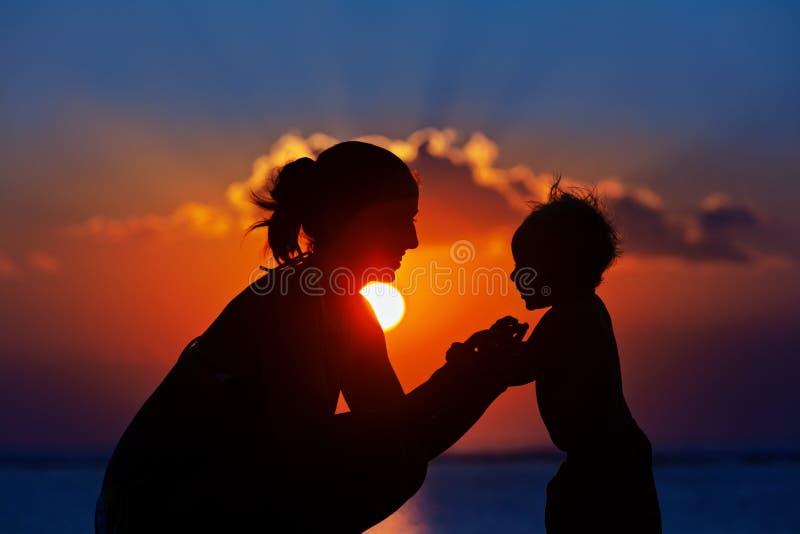 Silhueta preta da m?e, caminhada do filho do beb? pela praia do mar foto de stock