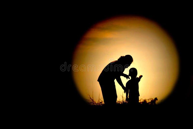 A silhueta preta da mamã e das crianças que olham a lua fotografia de stock royalty free