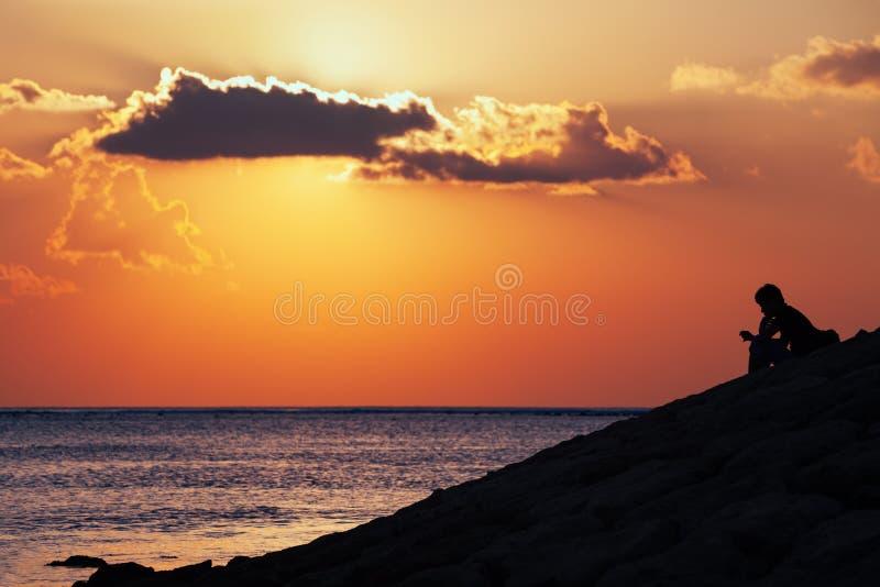 Silhueta preta do homem de pensamento que senta-se apenas na praia do mar imagens de stock royalty free