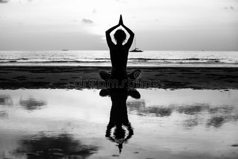 Silhueta preto e branco da mulher da ioga que medita na costa de mar relaxe fotografia de stock