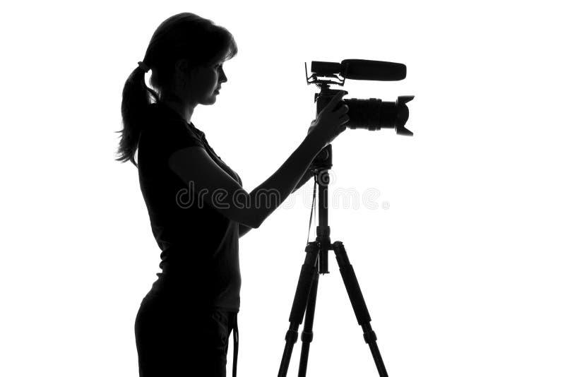 Silhueta preto e branco da mulher que está ao lado do equipamento vídeo e do trabalho com ele fotografia de stock