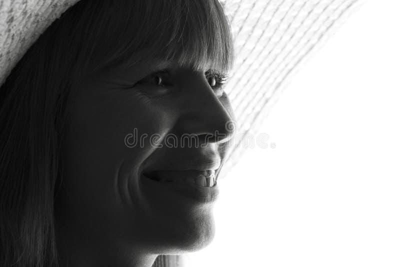 A silhueta preto e branco do retrato da forma de uma jovem mulher em um chapéu com a borda larga no branco isolou o fundo fotos de stock
