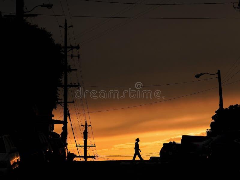 Silhueta que anda ao longo da estrada no por do sol fotos de stock