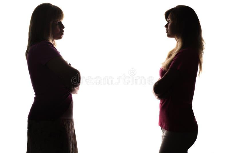 Silhueta que está oposto a se a filha e a mãe fotografia de stock royalty free