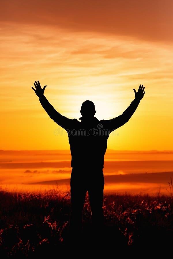 A silhueta rezando do homem no nascer do sol foto de stock