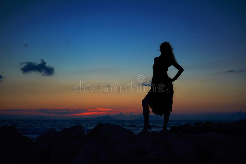 A silhueta romântica da mulher bonita nova bonita no por do sol irradia-se na areia do mar e na praia da pedra Mulher lindo no so imagens de stock