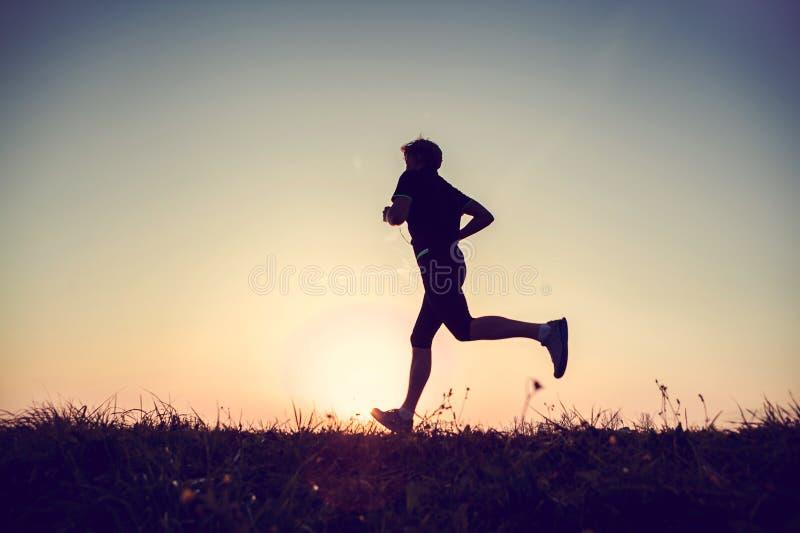 Silhueta running do homem no tempo do por do sol foto de stock royalty free