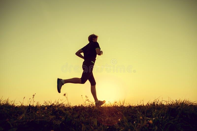 Silhueta running do homem no tempo do por do sol fotografia de stock