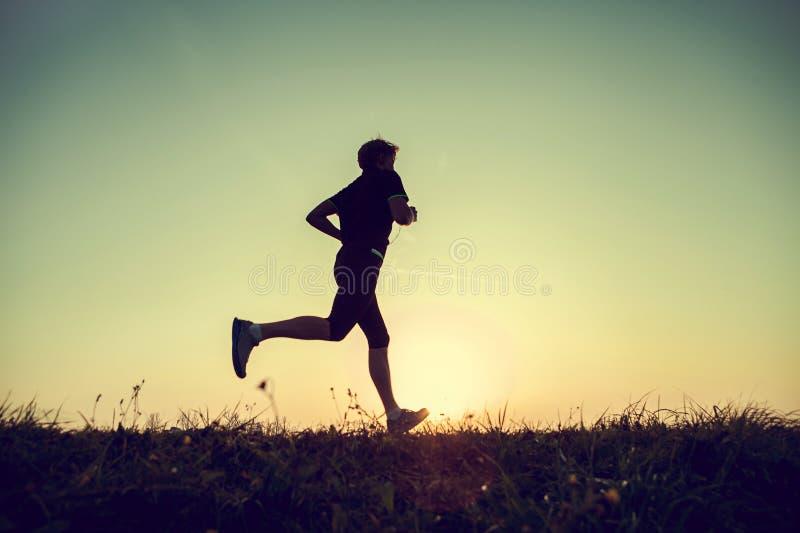 Silhueta running do homem no tempo do por do sol imagem de stock royalty free