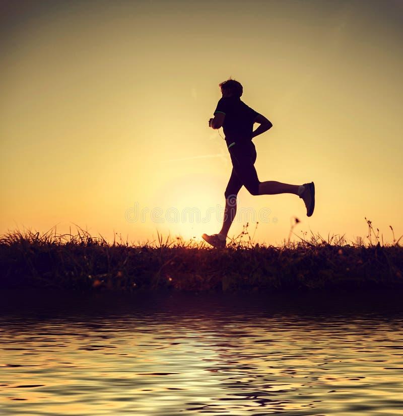 Silhueta running do homem no tempo do por do sol foto de stock