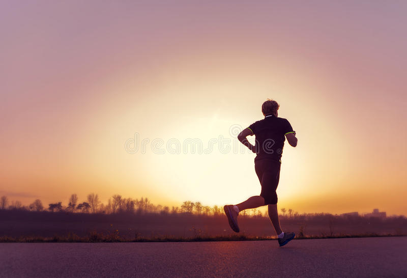 Silhueta running do homem no tempo do por do sol imagens de stock