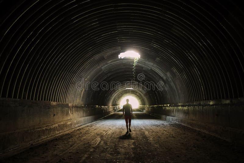 A silhueta só no túnel escuro vai à luz Homem que anda à luz fotografia de stock royalty free