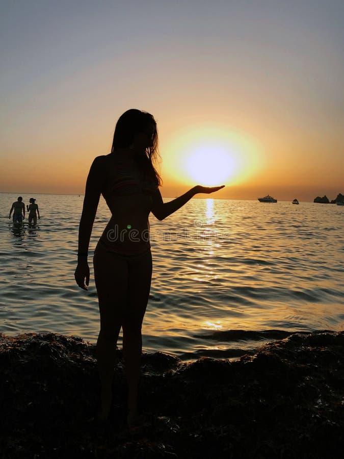 Silhueta 'sexy' da jovem mulher em um Sandy Beach durante um por do sol imagens de stock royalty free