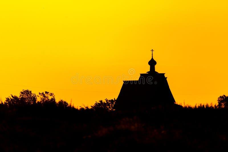 Silhueta transversal da igreja do por do sol em nuvens do céu do por do sol Silhueta da igreja do por do sol fotografia de stock