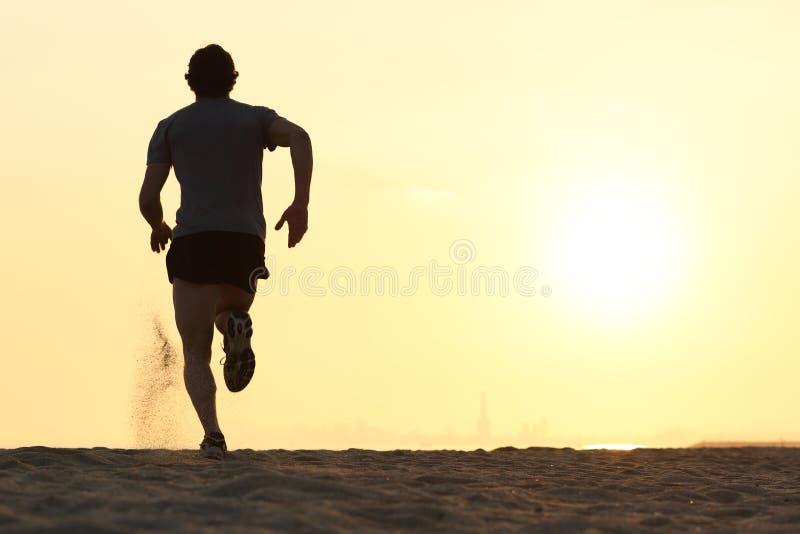Silhueta traseira da vista de um homem do corredor que corre na praia imagens de stock