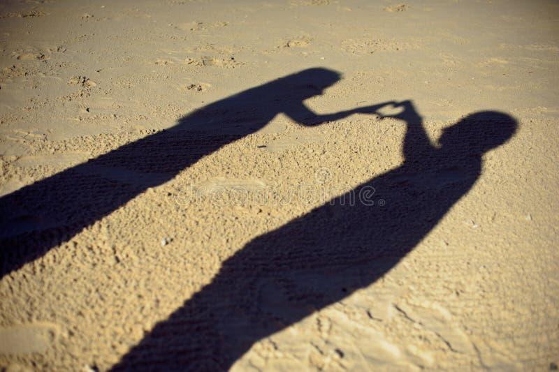 Silhuetas da fotografia dos pares ou dos dois amantes junto, sombra na terra, gesto da mulher um braço coração-dado forma, concei imagens de stock royalty free