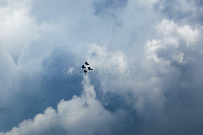 Silhuetas da manutenção programada quatro Su-30, aviões de lutador do russo altos no céu nebuloso azul fotos de stock