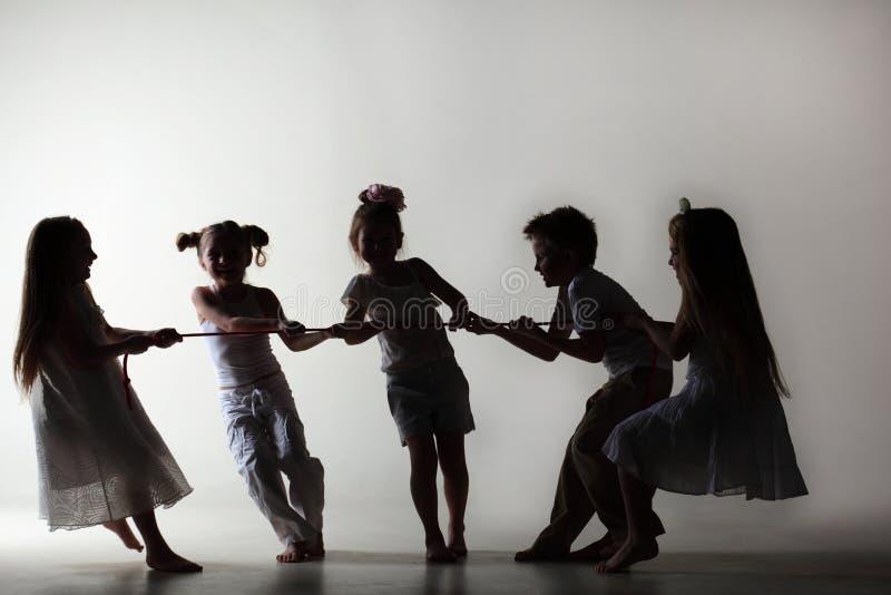 Silhuetas de crianças pequenas no desenho branco sobre a corda foto de stock