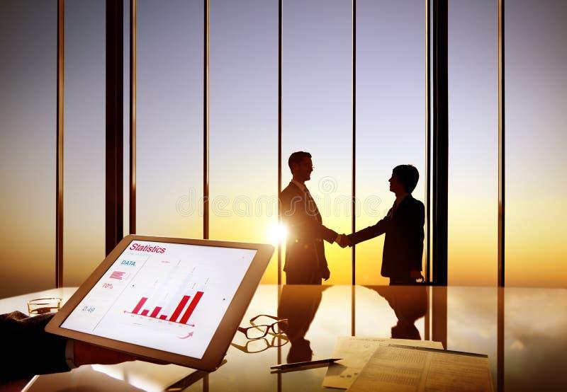 Silhuetas de dois homens de negócios que agitam as mãos junto em uma sala de direção fotos de stock