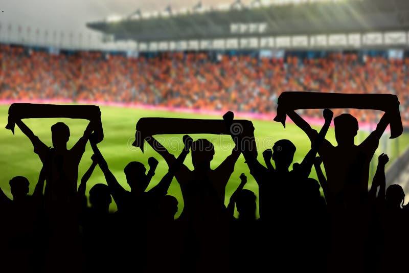 silhuetas de fãs de futebol em um fósforo e em espectadores no futebol imagens de stock