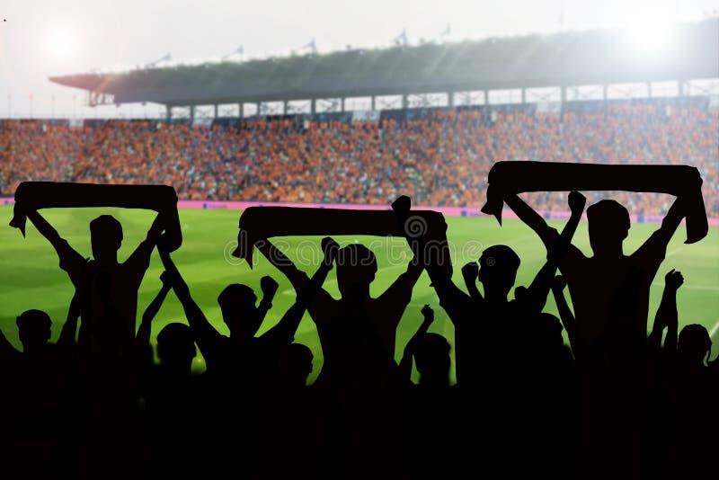 silhuetas de fãs de futebol em um fósforo e em espectadores no futebol foto de stock royalty free