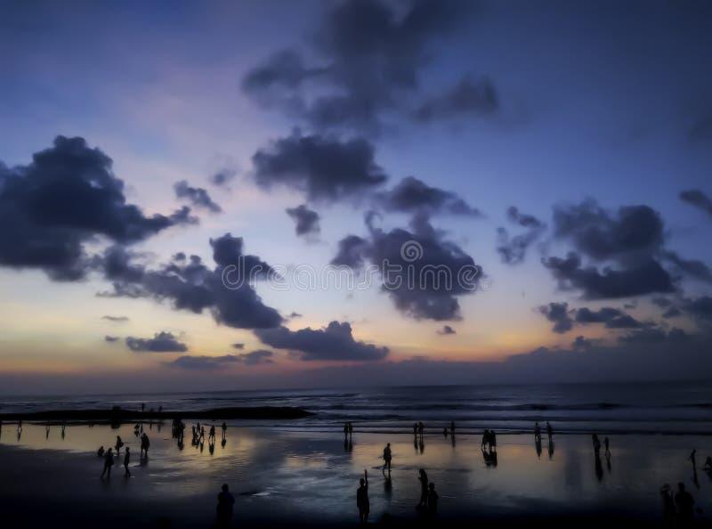 Silhuetas de povos desconhecidos na frente do oceano da noite, Bali, Indonésia imagem de stock