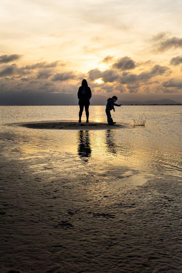 Silhuetas de povos irreconhecíveis na praia no por do sol fotografia de stock