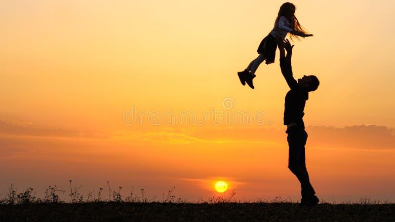 Silhuetas de precipitações felizes da criança nas mãos do pai imagens de stock